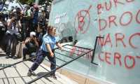 A demonstrator vandalizes a Chivo Wallet Bitcoin ATM during a protest against President Nayib Bukele's policies on Independence Day in San Salvador, on September 15, 2021. - Thousands of Salvadorans demonstrated on Wednesday to demand that President Nayib Bukele respect the separation of powers and reject the introduction of bitcoin as legal tender, just as the country commemorates the bicentenary of its independence. (Photo by MARVIN RECINOS / AFP)