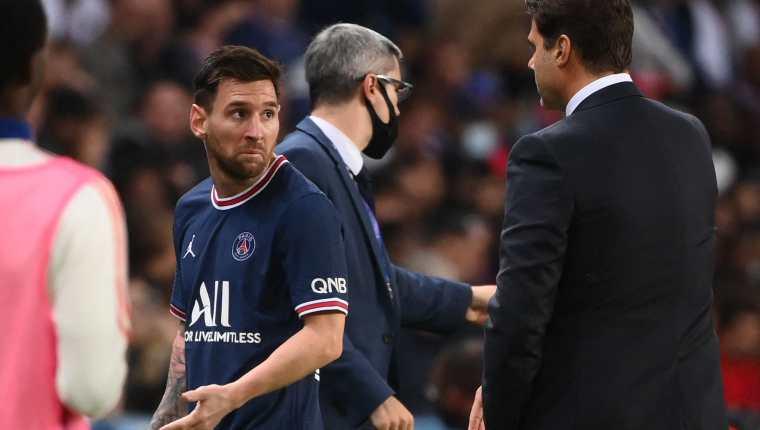 El jugador del Paris Saint-Germain Lionel Messi (izq) deja el campo mientras habla con Mauricio Pochettino en el partido ante el  Olympique Lyonnais en el Parc des Princes. (Foto Prensa Libre: AFP)