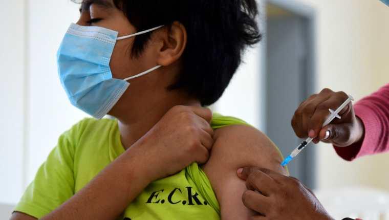 Foto de archivo que muestra a un menor de edad que recibe su dosis de vacuna contra el covid-19 de  Pfizer-BioNTech. (Foto Prensa Libre: AFP)