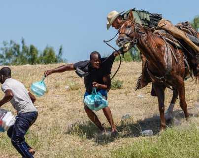 Un agente de la Patrulla Fronteriza a caballo tratar de evitar que un migrante haitiano ingrese a un campamento a orillas del Río Grande, cerca del Puente Internacional Acuña del Río en Del Río, Texas. (Foto Prensa Libre: AFP)