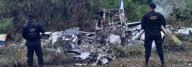 Agentes de la PNC resguardan los restos de una avioneta quemada, en San Luis, Petén, para que peritos del MP recaben evidencias. (Foto Prensa Libre: PNC)