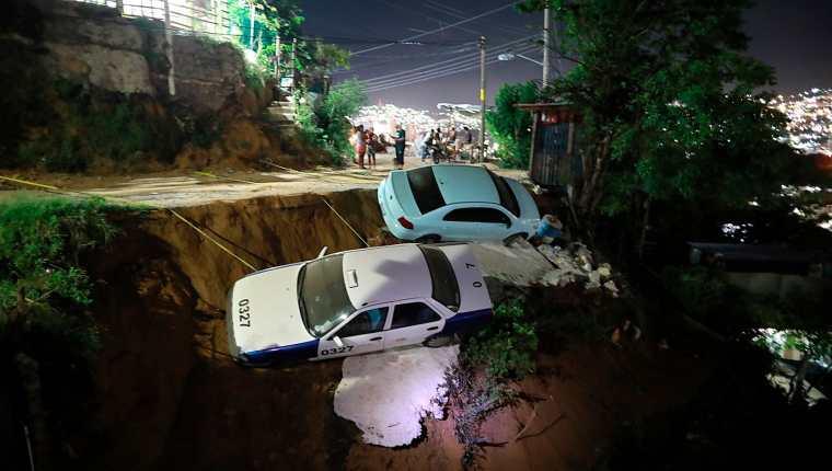 Dos vehículos quedaron a punto de caer a un barranco por el suelo reblandecido, debido al sismo de 7.1, en el balneario de Acapulco, Guerrero.  (Foto Prensa Libre: EFE)