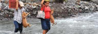 Pobladores cruzan a pie el río Mineral debido a que no se puede cruzar en vehículo. (Foto Prensa Libre: Byron García)