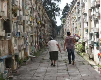 Varias personas llegaron a los cementerios a adornar las tumbas de sus seres queridos. (Foto Prensa Libre: Erick Ávila)