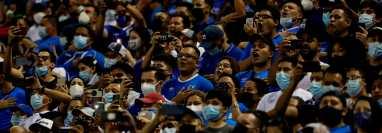 Aficionados salvadoreños cantan el himno nacional durante el juego entre El Salvador y México, en su juego de octogonal por las eliminatorias al mundial Catar 2022, hoy en el Estadio Cuscatlán en San Salvador. (Foto Prensa Libre: EFE)