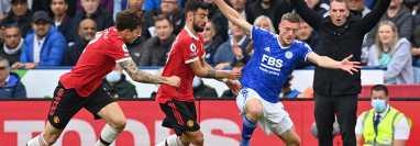 El defensa del Manchester United Victor Lindelof (izquierda) y su compañero Bruno Fernandes (centro) disputan el balón al delantero del Leicester City, Jamie Vardy (azul) ante la mirada de su entrenador Brendan Rodgers (atrás). (Foto Prensa Libre: AFP)