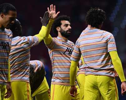 El delantero del Liverpool Mohamed Salah (centro) calienta con sus compañeros antes de medirse al Atlético de Madrid en la UEFA Champions League. (Foto Prensa Libre: AFP)