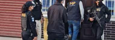 Fiscales del MP y agentes de la PNC en uno de los operativos contra una banda de falsificación de documentos de viaje e identidad que eran enviados a migrantes en Estados Unidos. (Foto Prensa Libre: MP)